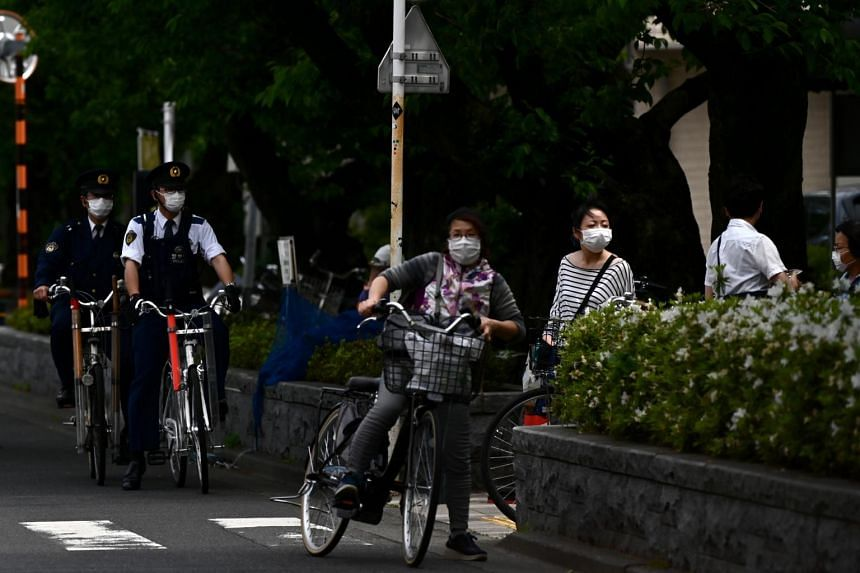 Policemen wearing face masks patrol in a street of Tokyo on May 3, 2020.