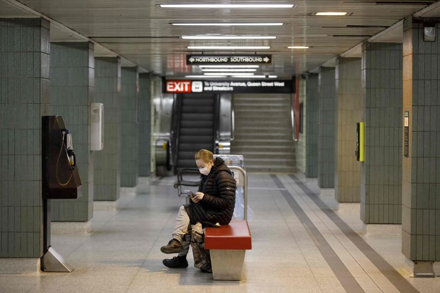 In a photo taken on April 1, 2020, a woman looks at her phone as she waits for the subway in Toronto.