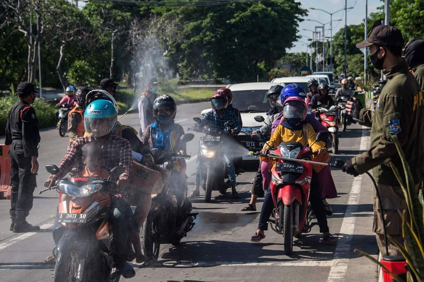 Officials disinfect motorists from Madura islands before entering Surabaya, on April 10, 2020.