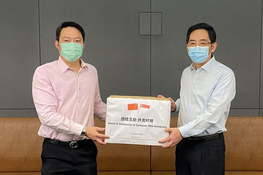 Singapore's Senior Minister of State Lam Pin Min (left) receives a donation of masks from China's ambassador to Singapore Hong Xiaoyong at the Ministry of Health on May 5, 2020.