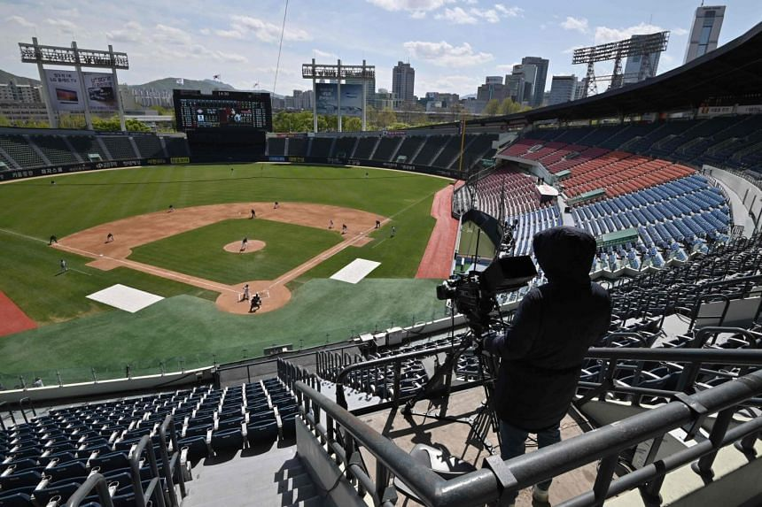 A cameraman is seen among empty stands during a pre-season baseball game at a stadium in Seoul on April 21, 2020.