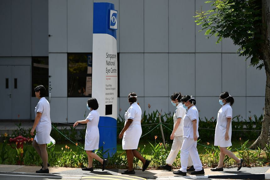 Nurses wearing face masks walk outside the Singapore National Eye Centre on March 7, 2020.