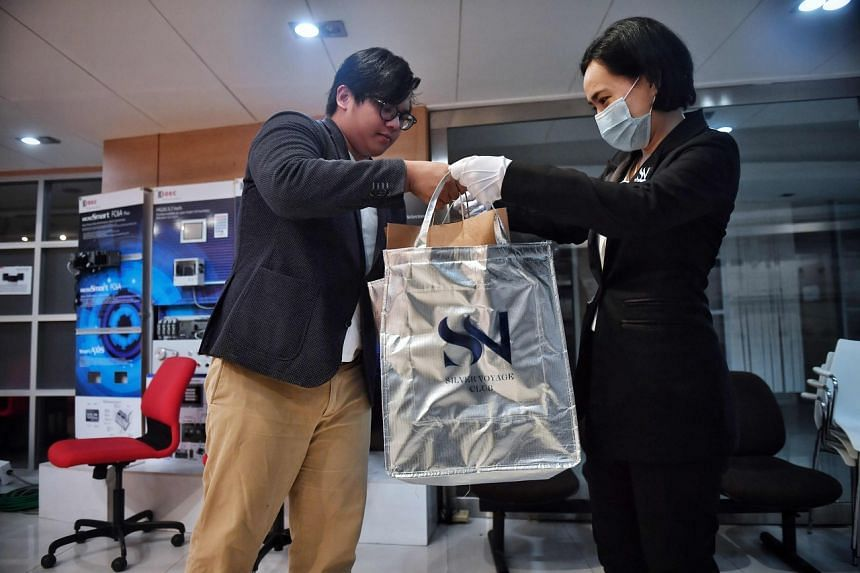An employee (right) from White Glove Delivery bringing an order to Mr Ukrit Vanagosoom, deputy managing director of the company KW Metal Work, at his office in Bangkok.