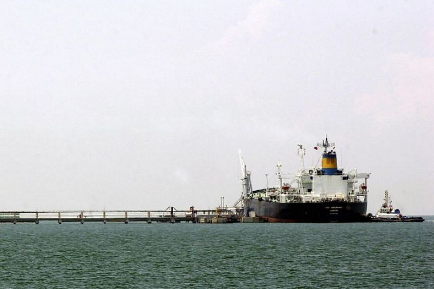 An oil tanker berths near storage tanks off Jurong island on Aug 25, 2005.