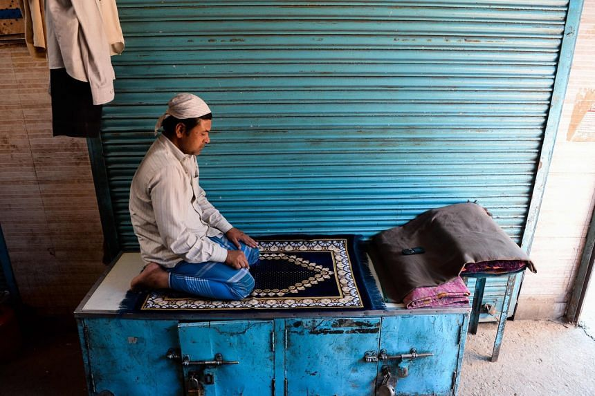A Muslim devotee prays in front of closed shops in a market, in New Delhi, on May 4, 2020.