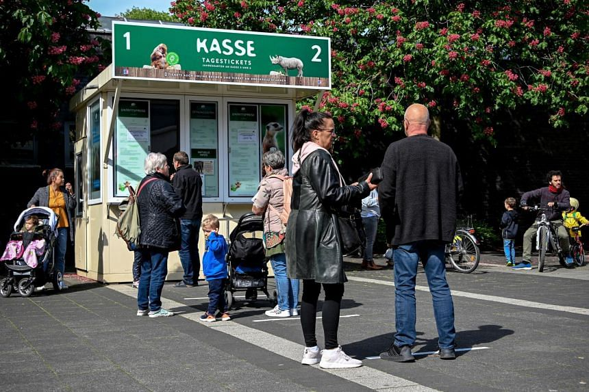 Visitors stand in line at the zoo's ticket office in Cologne, on May 5, 2020.