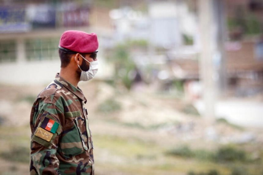 An Afghan security officer stands guard in the outskirts of Kabul.