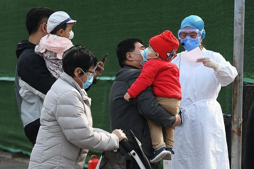 Families being screened by a hospital staff member while waiting to enter a children's hospital in Beijing in March, amid the coronavirus pandemic. In Singapore, Covid-19 has infected 57 children - those aged 16 and younger - but none has had to be i