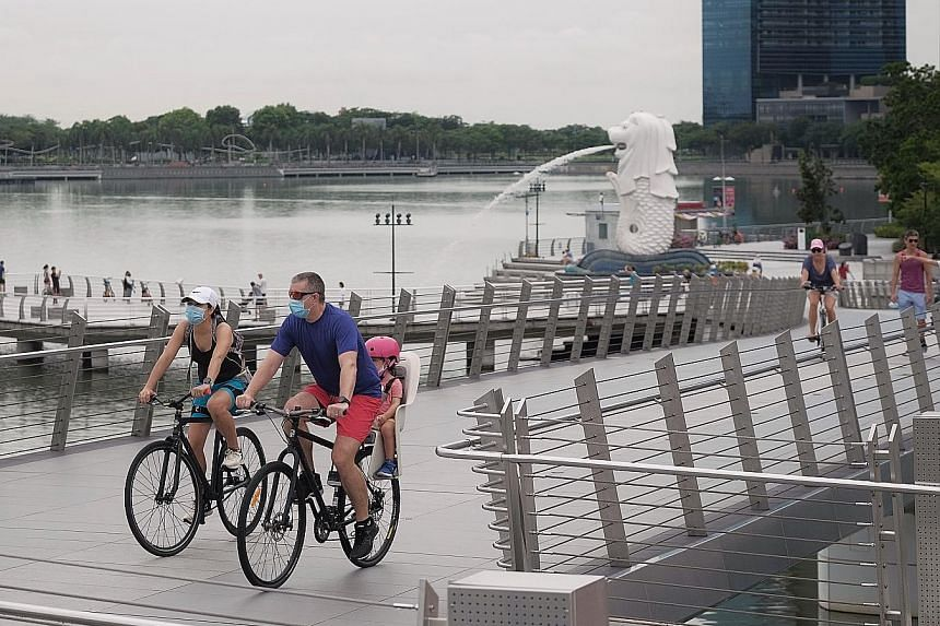 People cycling at Jubilee Bridge at the weekend. Yesterday was the 13th day in a row with new daily cases below 1,000. The total number of coronavirus cases in Singapore now stands at 20,198. ST PHOTO: GAVIN FOO