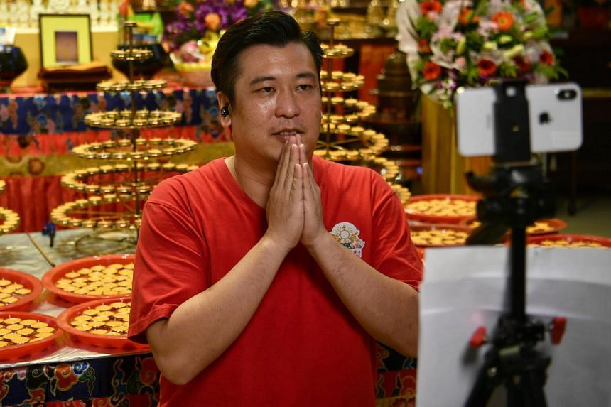 Temple Manager Bryan Long, with 1,000 candles behind him, speaks during a live stream at the Thekchen Choling temple on May 6, 2020.