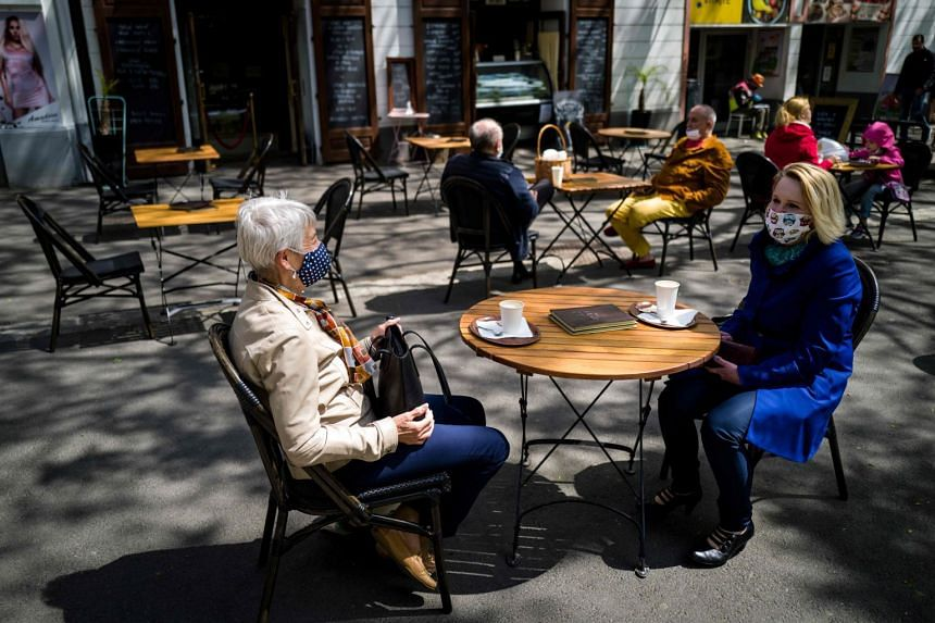 People sit at the terrace of a cafe in Bratislava on May 6, 2020, amid the coronavirus pandemic.