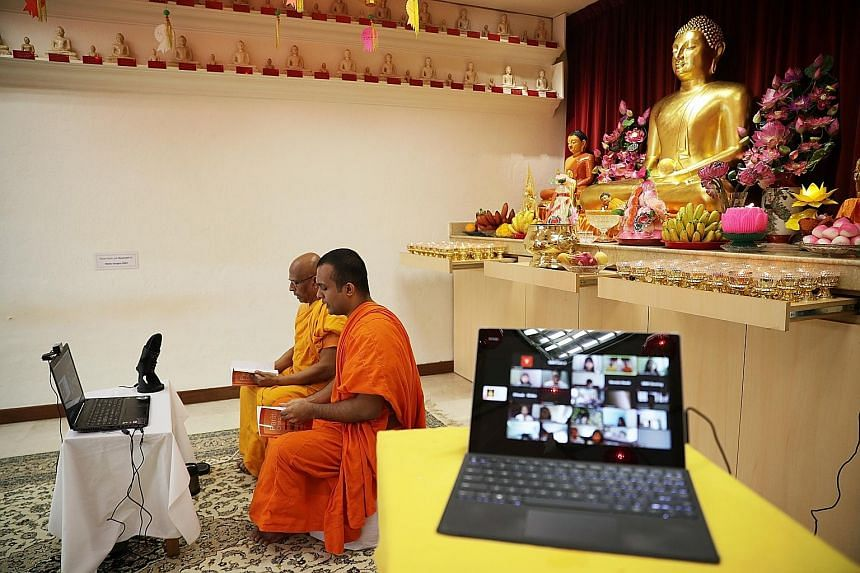 Singapore Buddhist Mission's Venerable K. Dhammika Maha Thera (left) and Venerable T. Chandima Thera conducting Pali chanting for a virtual audience yesterday, as Buddhists went online to commemorate Vesak Day.