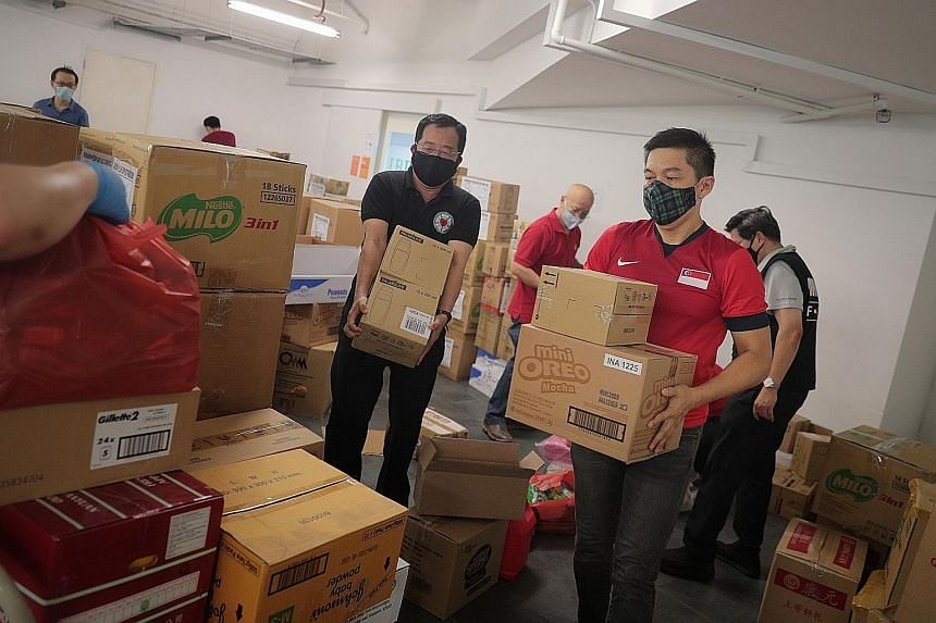 Speaker of Parliament Tan Chuan-Jin, Migrant Workers' Centre chairman Yeo Guat Kwang (in black vest behind him) and Singapore Kindness Movement general secretary William Wan (background, in red) helping with care packs for migrant workers at the Bibl