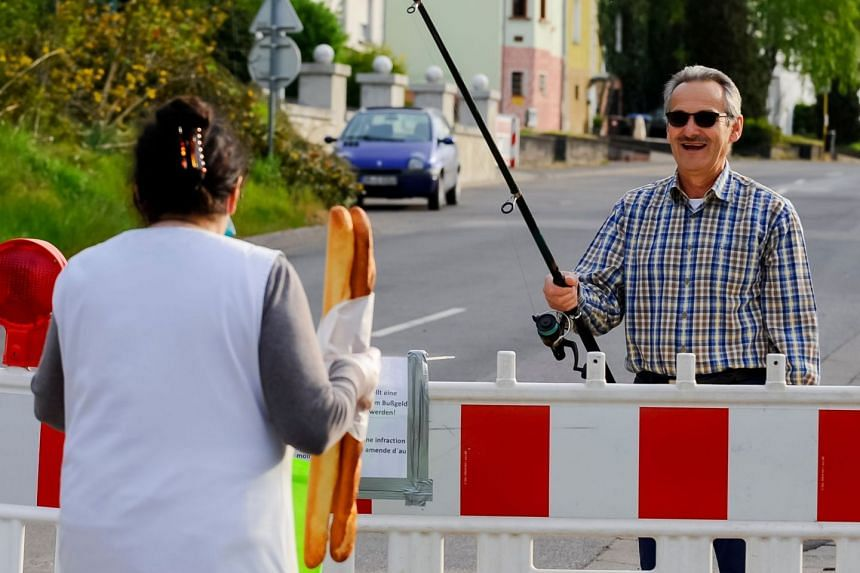 Hartmut Fey, a German citizen, gets his French baguettes at the German-French border using a fishing rod to avoid a fine on April 18, 2020,