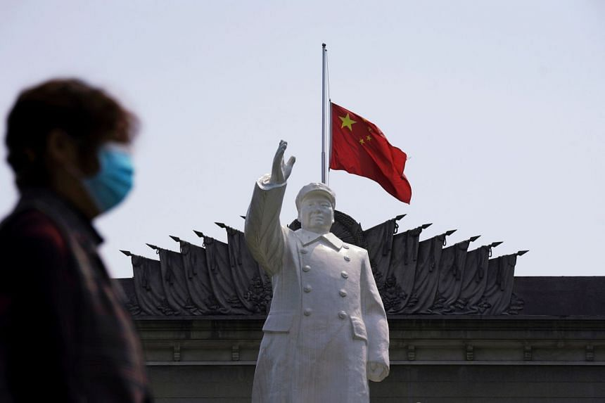The Chinese national flag flying at half-mast behind a statue of late Chinese chairman Mao Zedong in Wuhan, April 4, 2020.