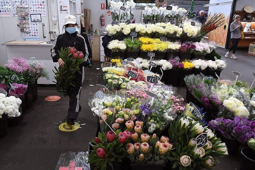 A florist in Melbourne making preparations for Mother's Day as Australia's government unveiled a three-stage plan yesterday to fully reopen the coronavirus-hit economy by July. The Reserve Bank of Australia has forecast that the economy would shrink