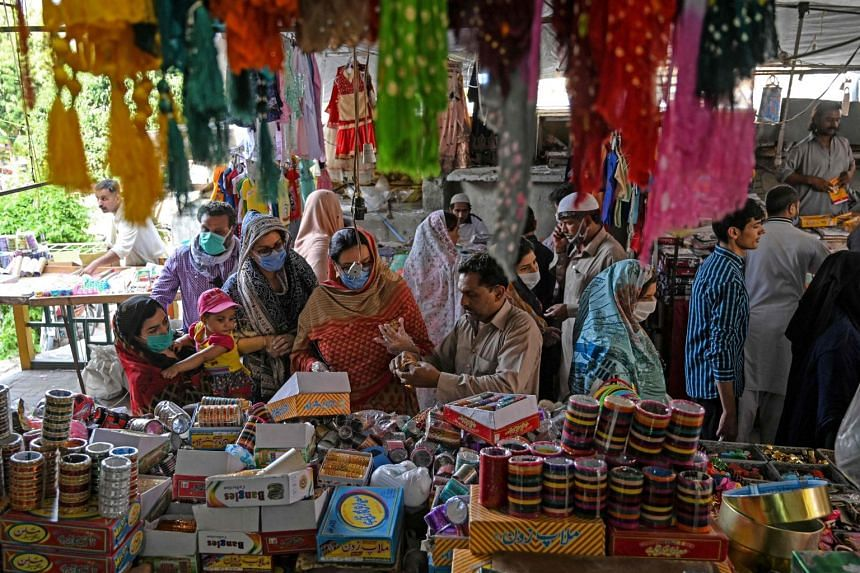 Customers shop for bangles at a market in Islamabad on May 9, 2020.