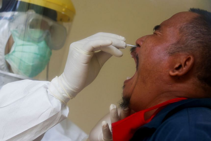 An Indonesian man getting a nasal swab. Indonesia has reported 12,776 cases and 930 deaths from the highly contagious Covid-19.