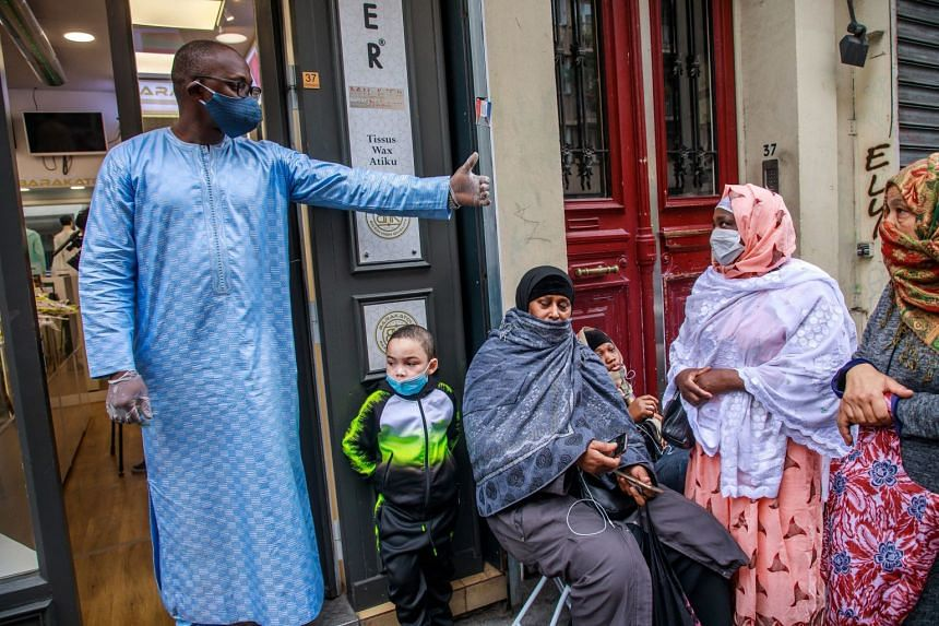 People queue outside Barakatou clothing store for free masks being given to residents of Paris' Goutte d'Or neighbourhood.