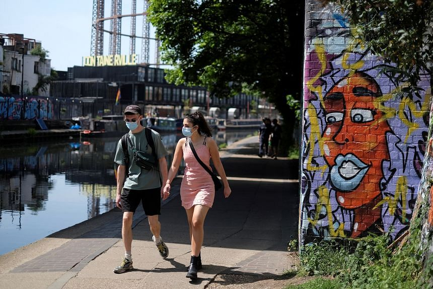 People walk along a tow path near Victoria Park in London, May 9, 2020.