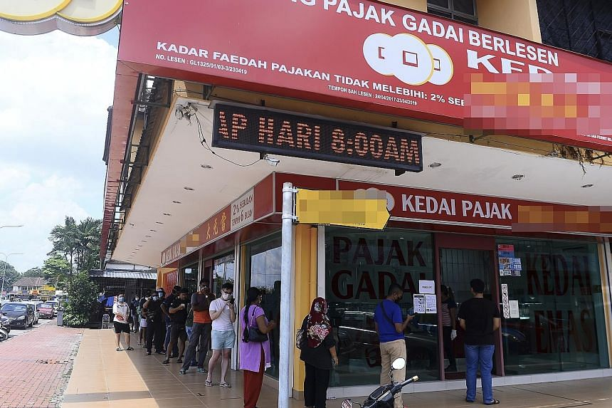 Long queues were seen outside pawnshops in Johor (above), Selangor, Melaka and other states in Malaysia as people pawned their jewellery for cash or renewed pawn tickets. Malaysia began relaxing its coronavirus control measures, allowing some busines
