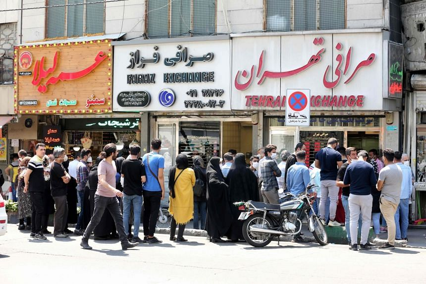 Iranians queue outside a money exchange office in the capital Teheran, on May 9, 2020.