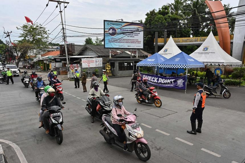 Motorists commute past a check point during a partial lockdown in Jakarta, on May 11, 2020.