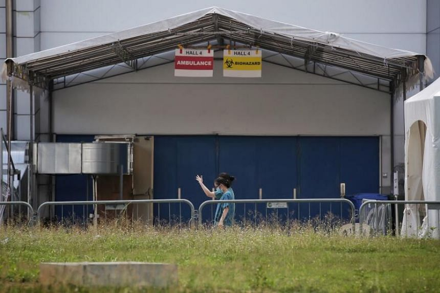 Healthcare workers walk past Hall 4 of the Singapore Expo, on May 8, 2020.