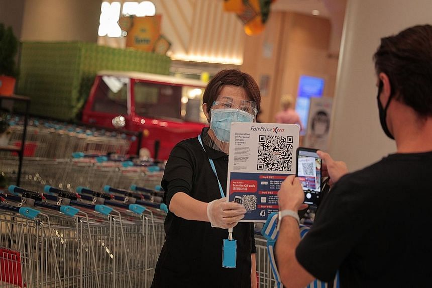 Left: A staff member holding up a QR code for a shopper to complete a contact tracing form before entering FairPrice Xtra at VivoCity last week. Below: A woman getting her temperature taken before entering a McDonald's outlet at White Sands mall yest