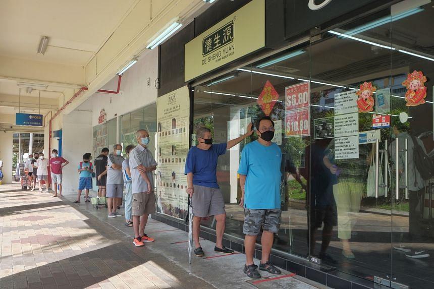 Customers queue at the Snip Avenue hair salon at Bishan Street 13, on May 12, 2020.