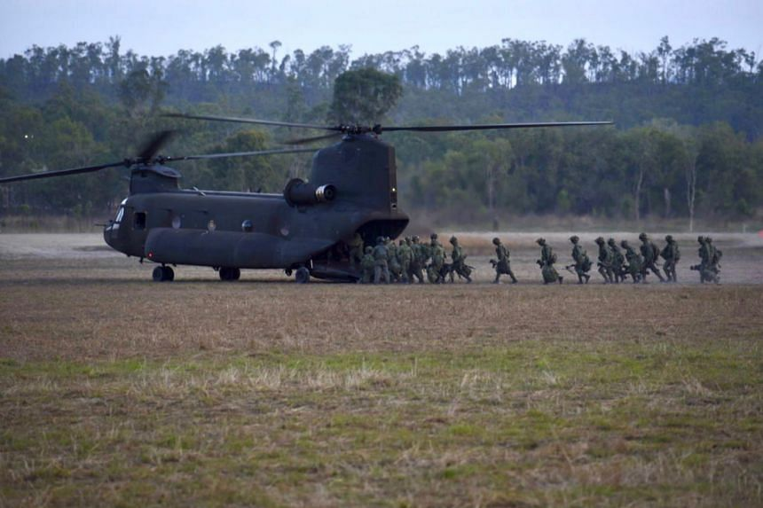 Soldiers embark a RSAF's Chinook helicopter for a troop-lift mission.