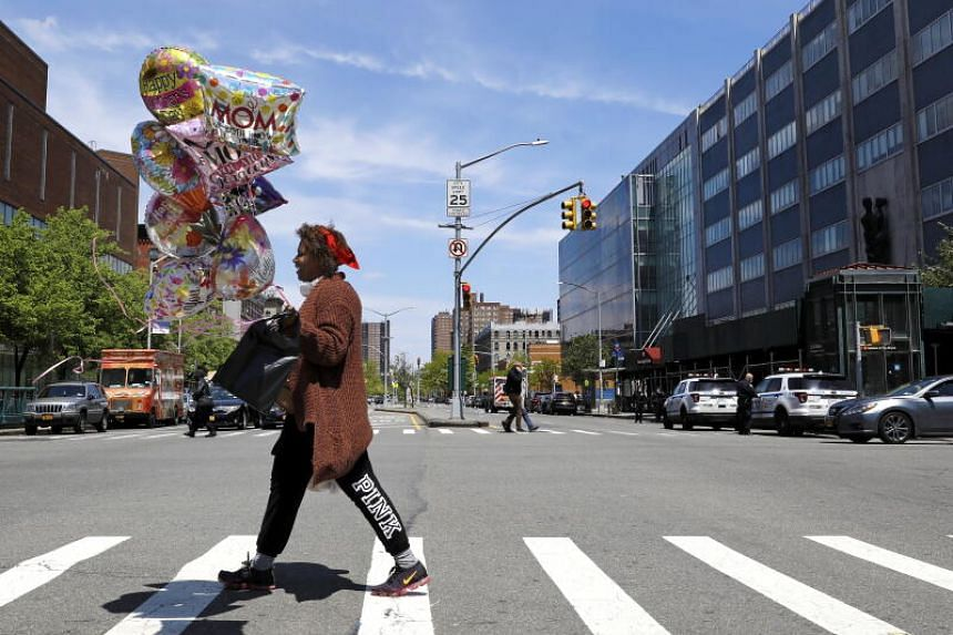 A woman crosses a road in Harlem, New York, on May 10, 2020.