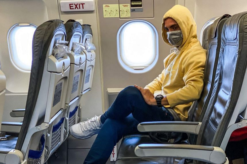 A passenger wears a face mask as a preventive measure on a flight between Frankfurt and Barcelona on March 17, 2020.