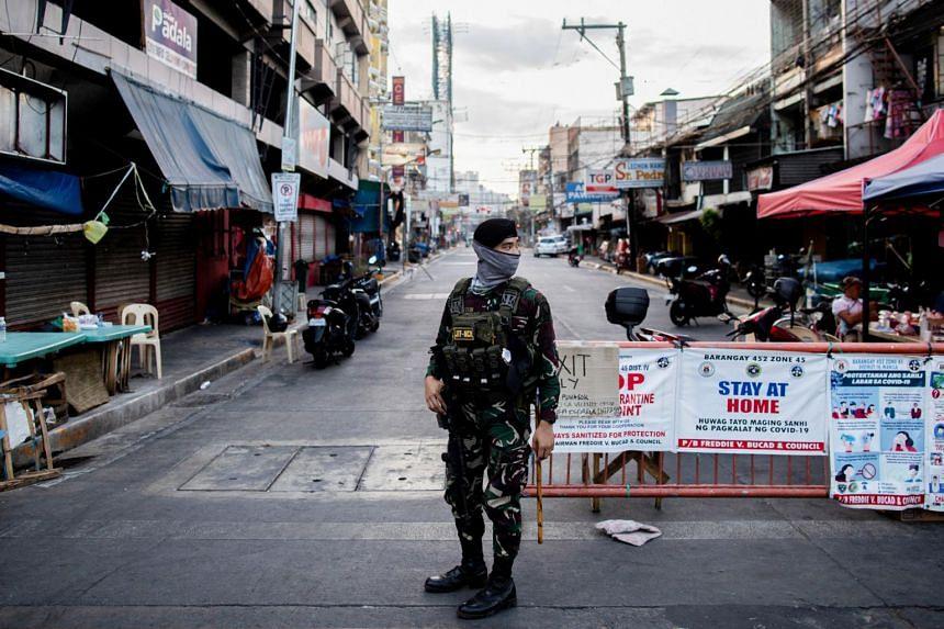 A soldier wearing a face mask guards an empty street  in Manila on April 24, 2020.