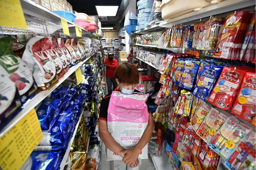 An  employee carrying a packet of cat food for a customer at Superpets pet shop on May 12, 2020.