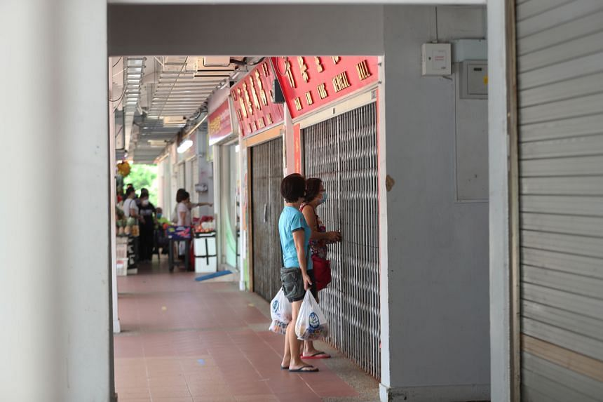 People making purchases from a traditional Chinese medicine shop through the shop gates.