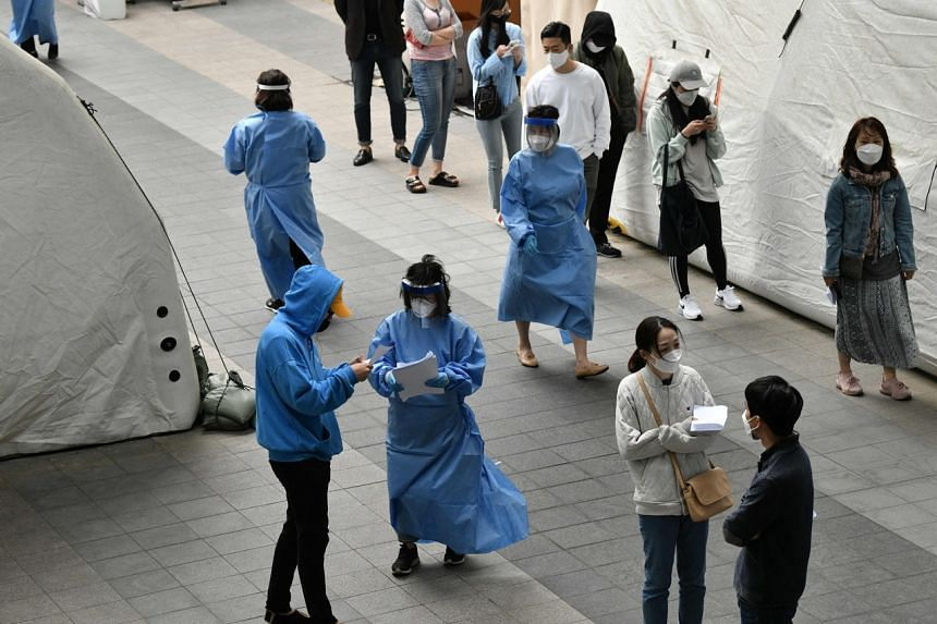 Medical staff members (in blue gowns) guide visitors waiting to take the coronavirus test in Itaewon, Seoul, on May 12, 2020.