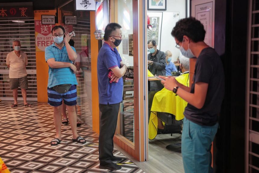 Customer queue outside a barber shop in Tiong Bahru Plaza as circuit breaker measures ease on May 13, 2020.