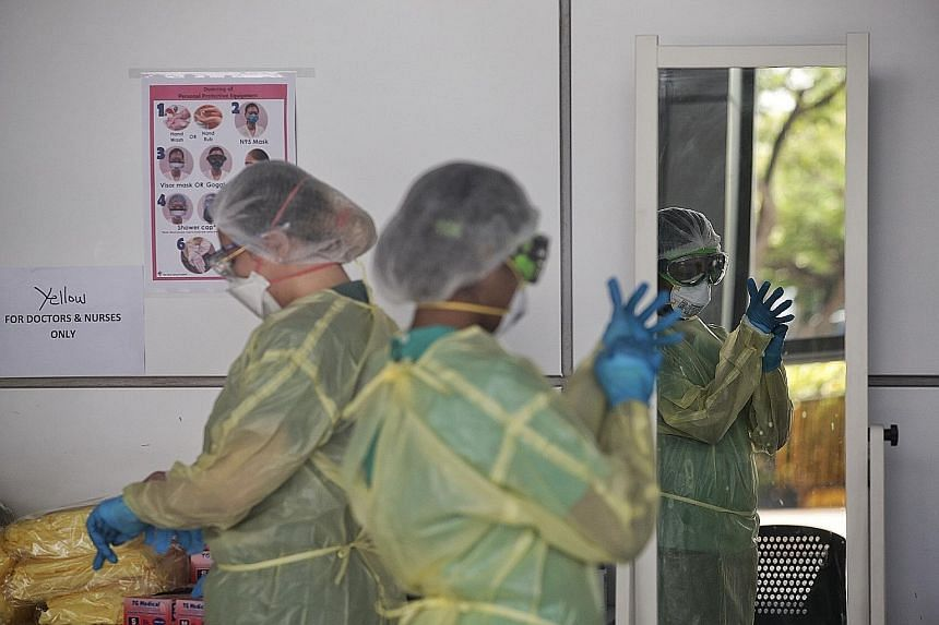 Healthcare workers donning their protective gear at the community isolation facility at Singapore Expo. Unlike Sars, which caused about 800 deaths, Covid-19 has caused a far higher death toll, with nearly 300,000 dead around the world so far. Scienti