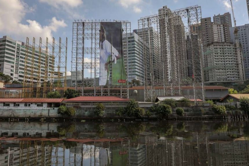 Workers remove a billboard advertisement in preparation for typhoon Vongfong, in Makati, Philippines, on May 14, 2020.