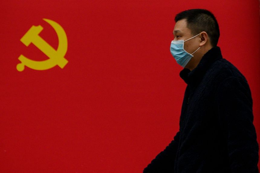 A man wearing a protective face mask walks past a Communist Party flag in Wuhan, China.
