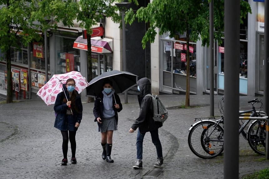 Schoolgirls walk in a street of Lausanne on their way to the school, on May 11, 2020.