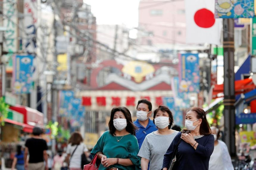 People make their way at a local market district in Tokyo on May 13, 2020.