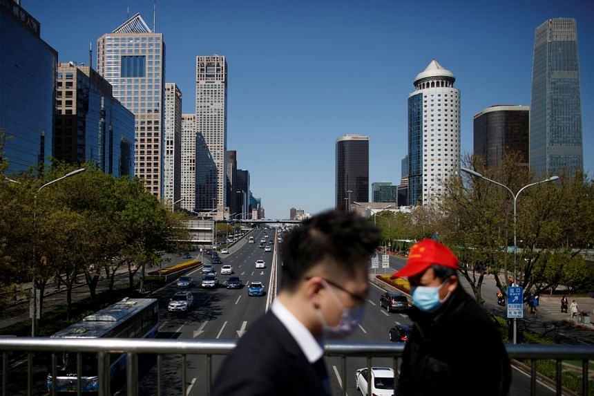 People cross a bridge at the Central Business District in Beijing on April 22, 2020.
