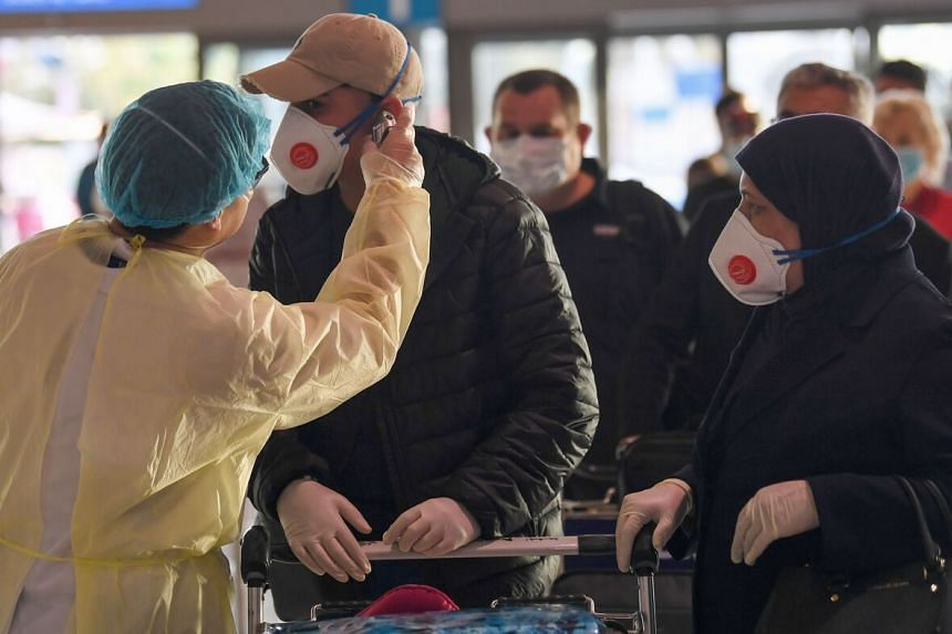 A health worker checks the body temperature of passengers bound for Frankfurt at Dubai International Airport, on April 6, 2020.
