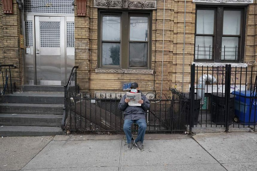 A man reads the newspaper on the sidewalk in Brooklyn, New York, on March 31, 2020.