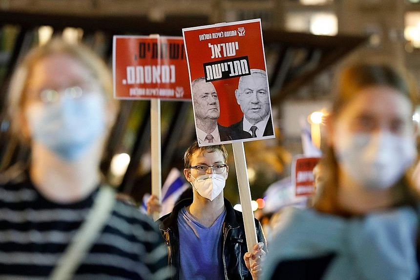 """A demonstrator holding a sign, with the faces of Israeli Prime Minister Benjamin Netanyahu (right) and Mr Benny Gantz, that says in Hebrew """"Israeli ashamed"""" in Rabin Square in Tel Aviv on May 9."""
