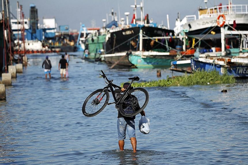 Fishermen making for safety at a seaport in Navotas City, Philippines, yesterday. Hundreds of thousands live in coastal areas and flimsy homes near where Typhoon Vongfong blasted ashore, and tens of millions more are on the storm's forecast path that