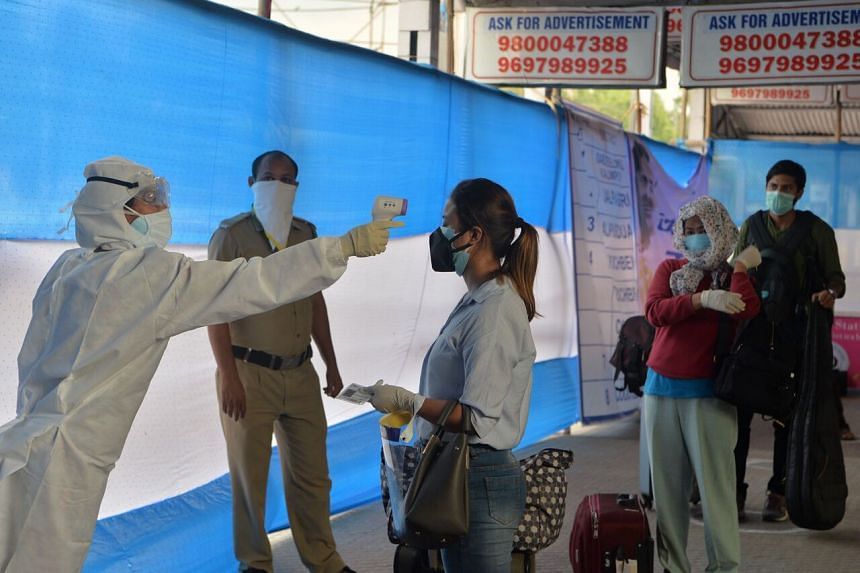 Health workers check the body temperature of passengers at New Jalpaiguri railway station, on May 13, 2020.