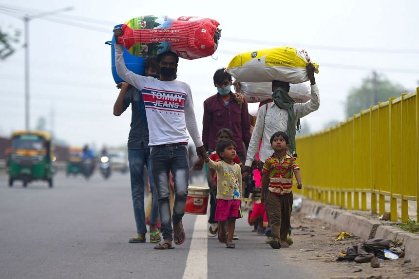 Migrant workers and their family members walk with their belongings towards their respective hometown states on May 13, 2020.